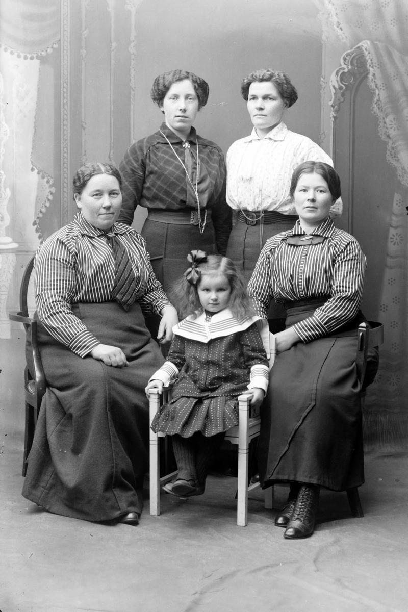 Studioportrett av en ung jente omgitt av fire kvinner.