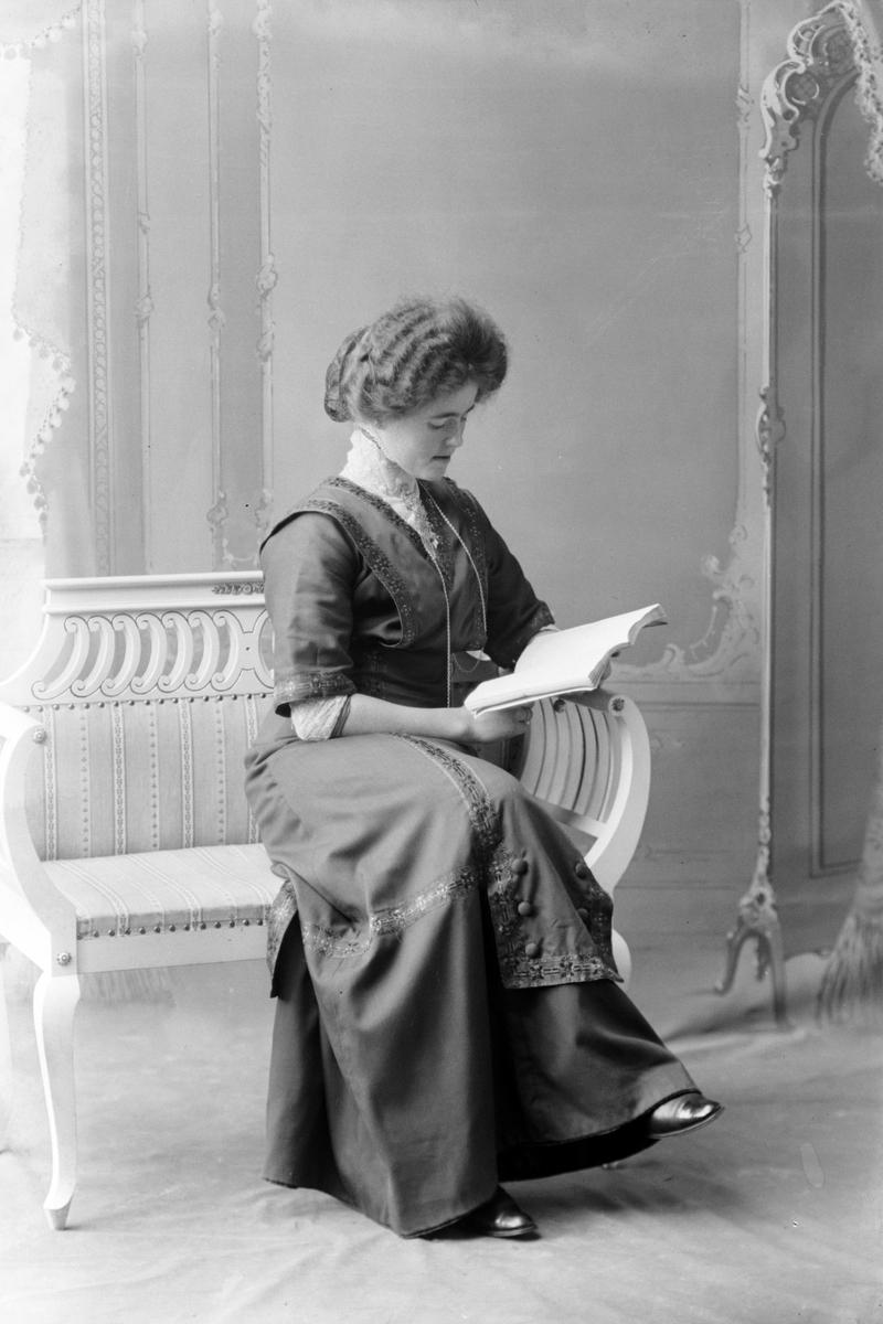 Studioportrett av en kvinne som leser en bok.