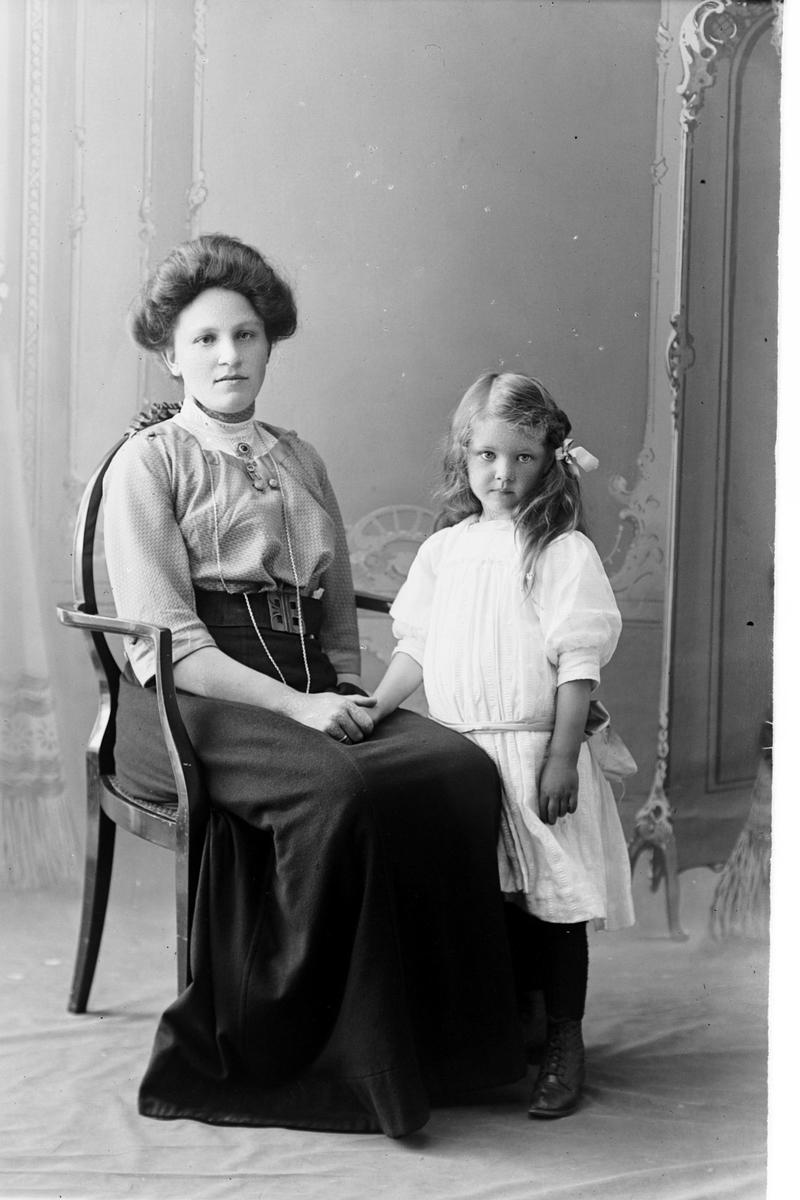 Studioportrett av en kvinne og en liten jente.