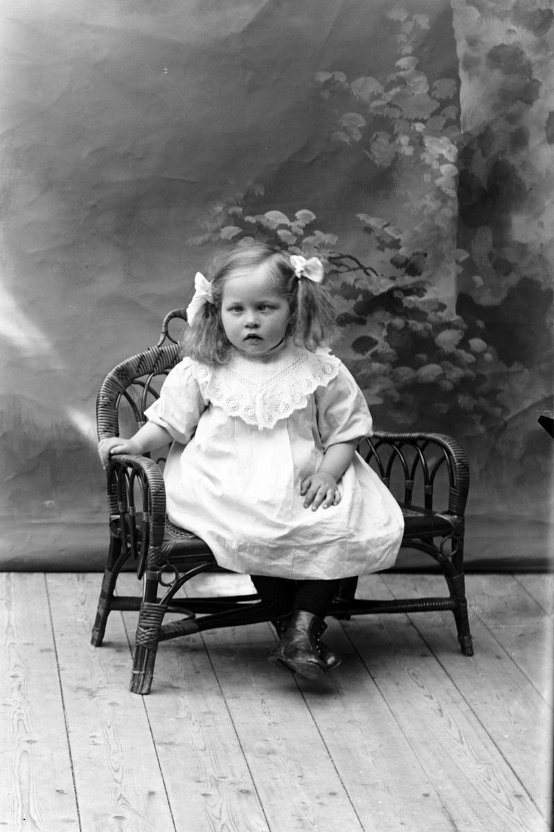Studioportrett av en jente sittende på en stol.