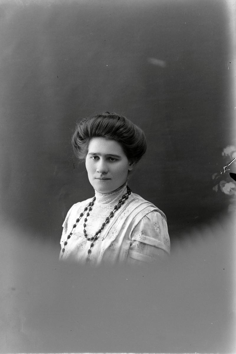 Studioportrett av en kvinne i halvfigur.