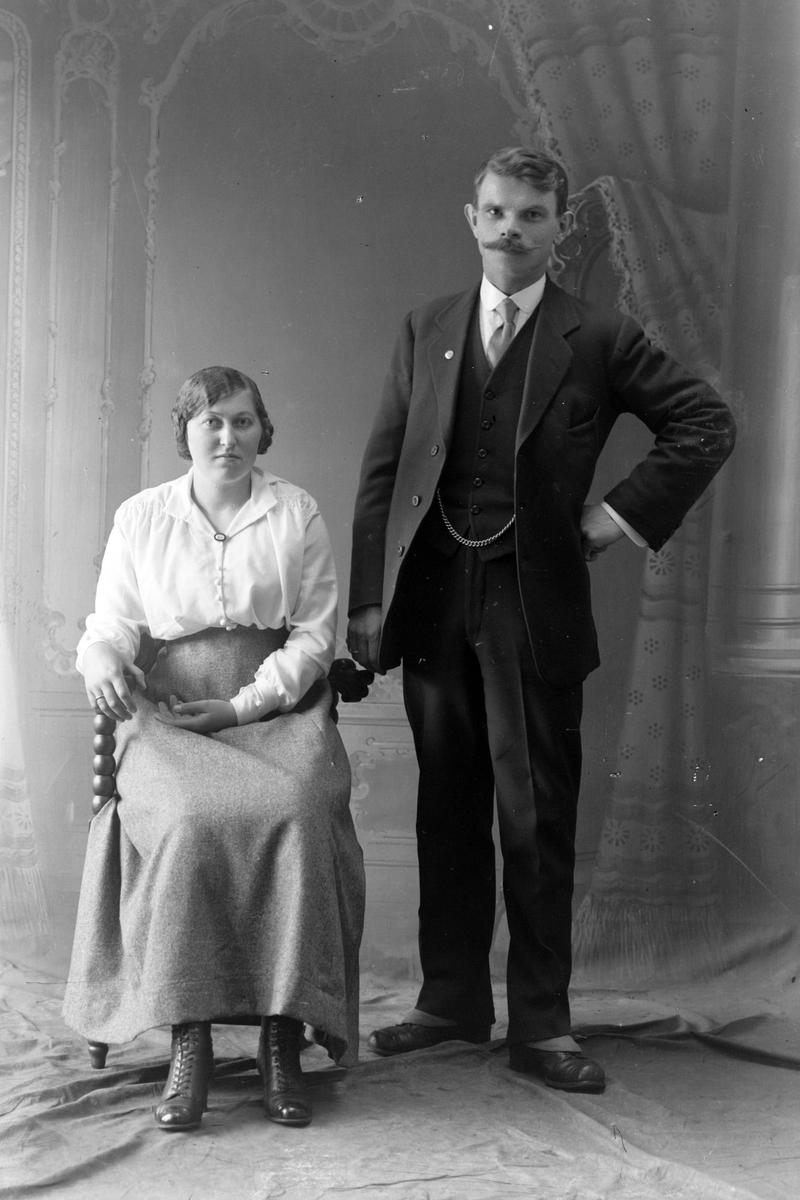 Studioportrett av en mann og kvinne i helfigur.