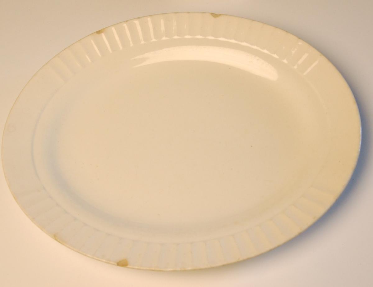 Ovalt porselen serveringsfat med bølgedekor rundt ytterkant av fatet.