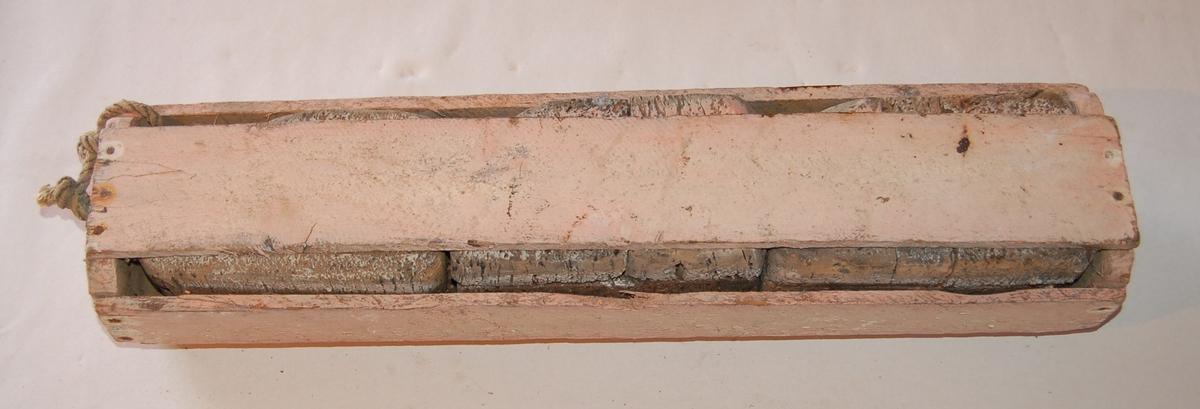 Korktrælen består av tre korker som er innkledd i ei tregrind for å binde dei samen.