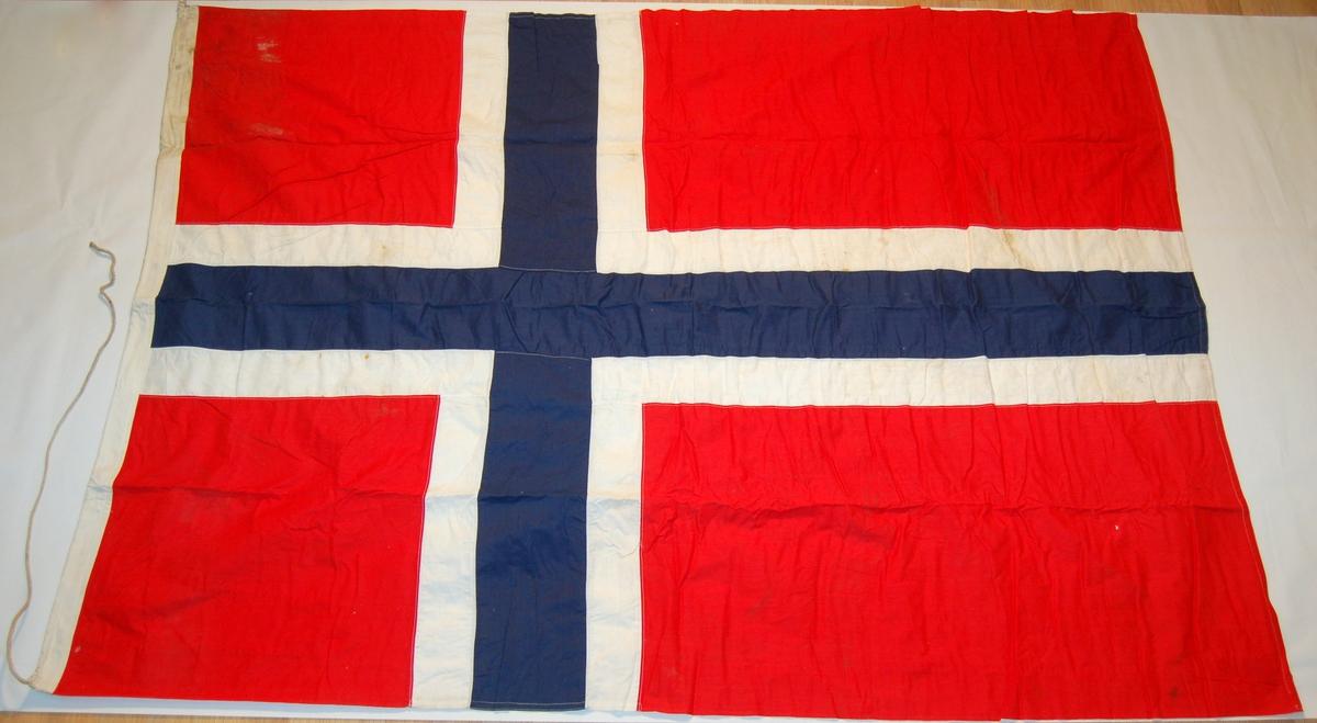 Norsk nasjonalflagg. Blått og kvitt kors på rød bunn.