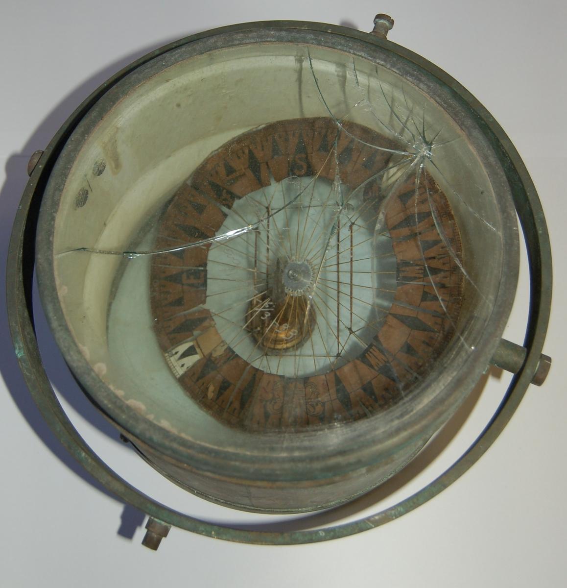 """Gjenstanden er eit """"Luftkompass"""" av eldre type. I glasset på kompasset er det ripet inn dateringer for når kompasset er korrigert. """"aa/912. 17-2-30"""" (17.02.1933). """"aa/233"""". """"aa/1195. 6/3-33"""" (06.03.1933)."""