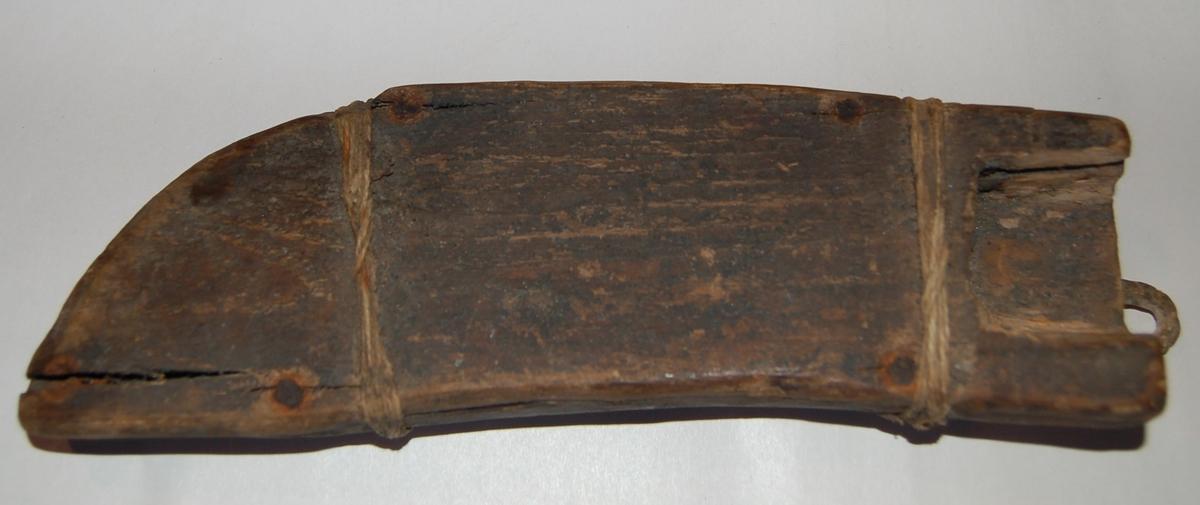 Svakt buet knivformet slire, benslet sammen på to steder med bensletråd. En beltestropp av tau er sydd/knytt fast i taubeltet i lag med den øverste benslingen av sliren.