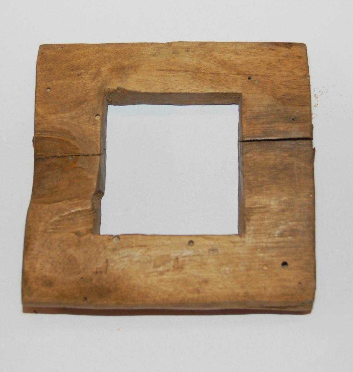 Elipseformet trestykke (kjevle) til garnbitting. I garnkjevlet er det utskjært et kvadratisk stykke på 4 x 4 cm.
