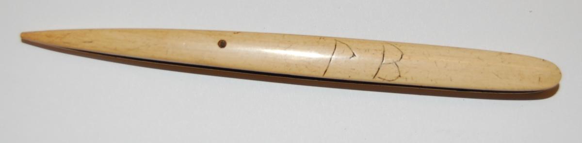 Nålen har en rektangulær form. I nålen er det utfreset et spor som tråden skal spoles opp på, og munnen på nålen er nebbformet med splittet ende.
