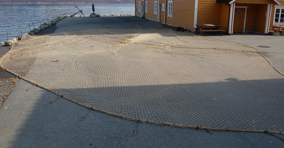 Handknytt nett med maskestorleik 7 x 7 cm. Til flåen er det festet 17 karabinkroker til å feste nettet til skipsrekka, og grynnen er belagd med blysøkker.