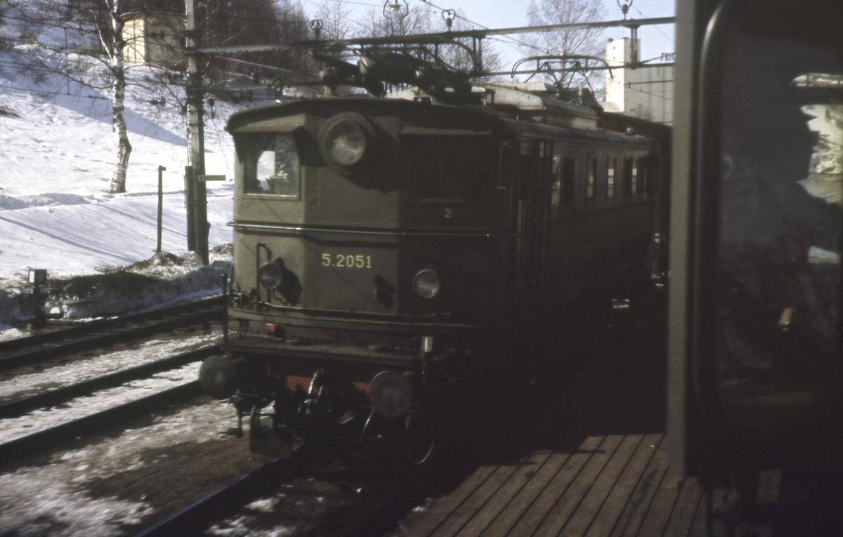 Kryssing på Eidsvoll stasjon mellom persontog retning Hamar og godstog retning Oslo, fotografert fra førerrommet på et elektrisk lokomotiv type El 13. Godstoget trekkes av elektrisk lokomotiv tye El 5.