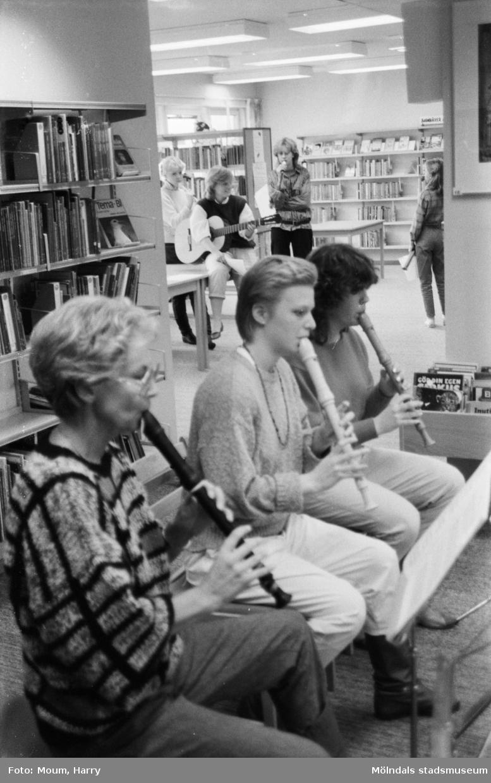 """Musik, dockor och konstutställning på Kållereds bibliotek, år 1984. """"Margret Jonsson, Anna Gustavsson och Anette Palmqvist musicerade i Kållereds bibliotek.""""  För mer information om bilden se under tilläggsinformation."""