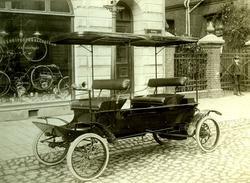 Bil parkerad på en kullerstensgata. Cykelaffär med text på g