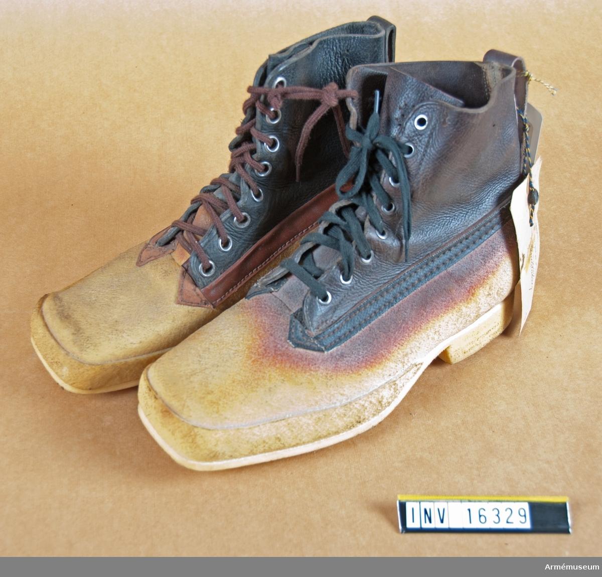 Gummipjäxa av rågummi m/1954. Med foten i rågummi och skaftet av läder som är mörkbrunt. Har snörning och sula och klack av rågummi. Höger pjäxa har brun skoning mellan fot och skaft samt brunt snöre, vänster har svart snörning och svart snöre.