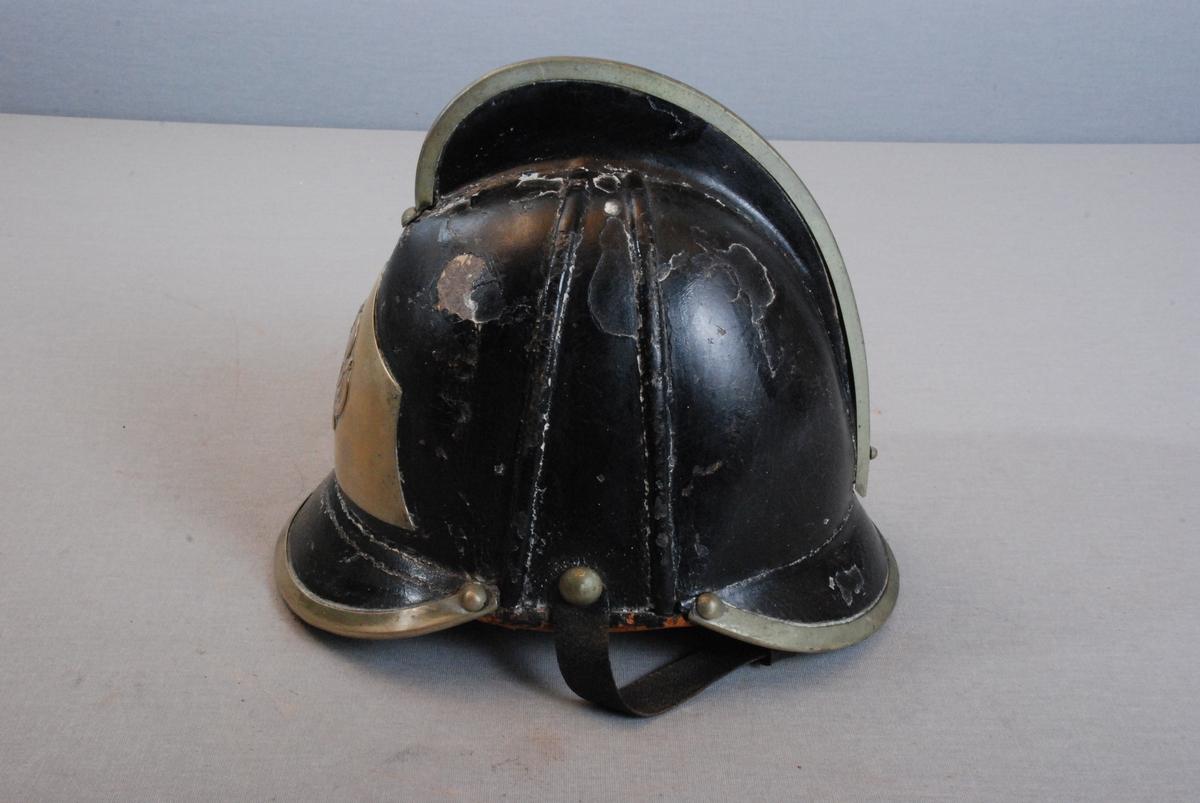 Brannhjelm i metall, med hanekam Metallkant påsatt på toppen. Hjelmen har brem foran og bak. Belagt med skinn på innsiden. Innerfor av skinn med hull for snorregulering. Hakereim i skinn. Hjelmen har Bergen byvåpen emblem. som dekor på  metallplate i front