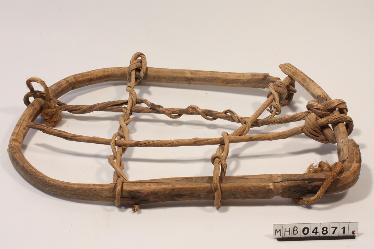 Stor oval/rektangulær kløvmeis laget av buet tre med vidjebåndsfletting.Det er to rader med vidjebånd i hver retning, og retningene er flettet sammen.To hampetau er festet rundt rammen i løkker. Meisen er brukket i det ene hjørnet. Nesten brukket av i et av de øvre festene for vidjebånd. Innfellinger i treet der vidjebåndene er festet. Spiker/jernsøm er brukt til feste av rammen.