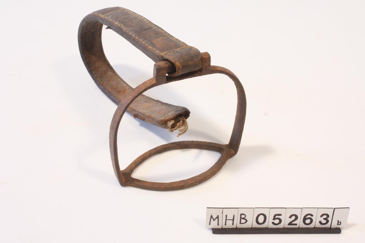 Stigbøyle av jern. Oval ring som underlag for fot. Spenne på oversiden til feste av lærreim. Lærreim følger med. Røket i motsatt ende.
