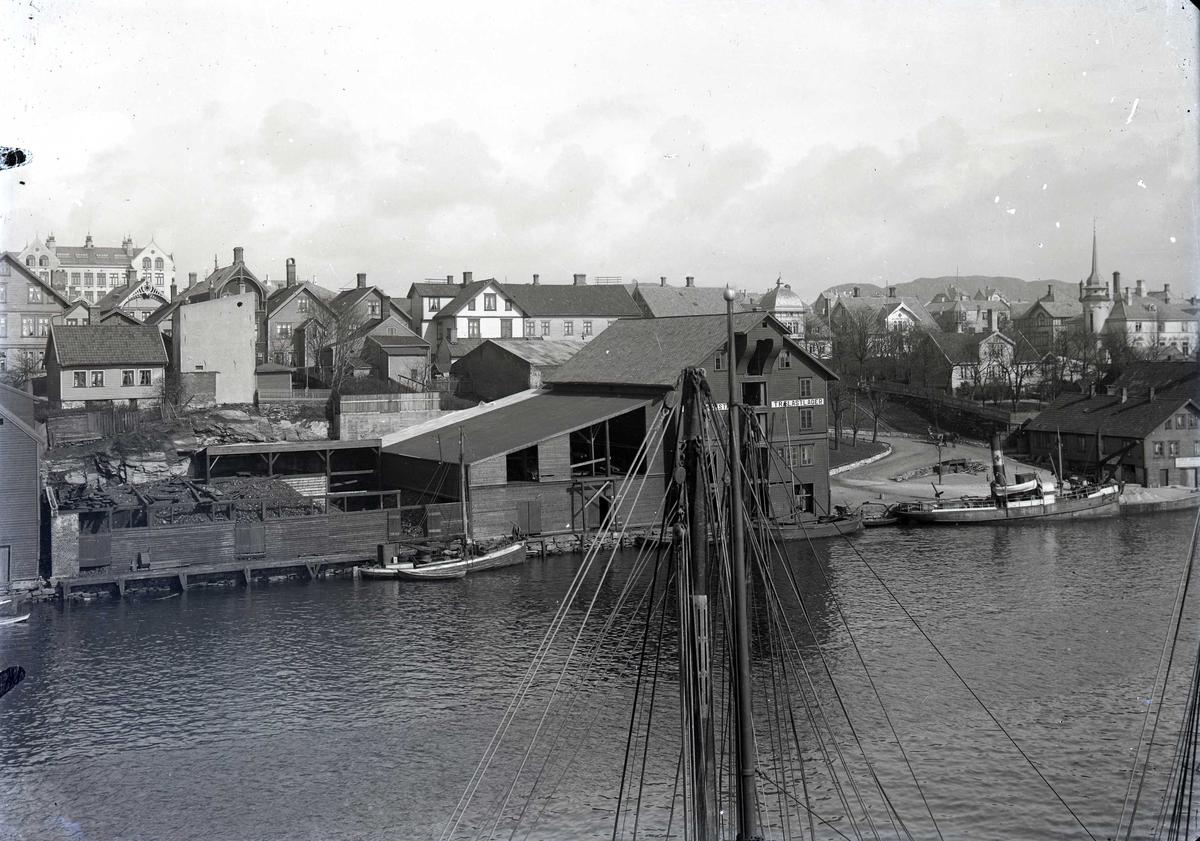 Havn - sjøhus - bymiljø. Sjøhusrekke sør i Smedasundet. Bak til høyre ses Strandgt. 92 med tårn og kuppel. Småfartøy til kai. Breidablikk skole i bakgrunnen til venstre.