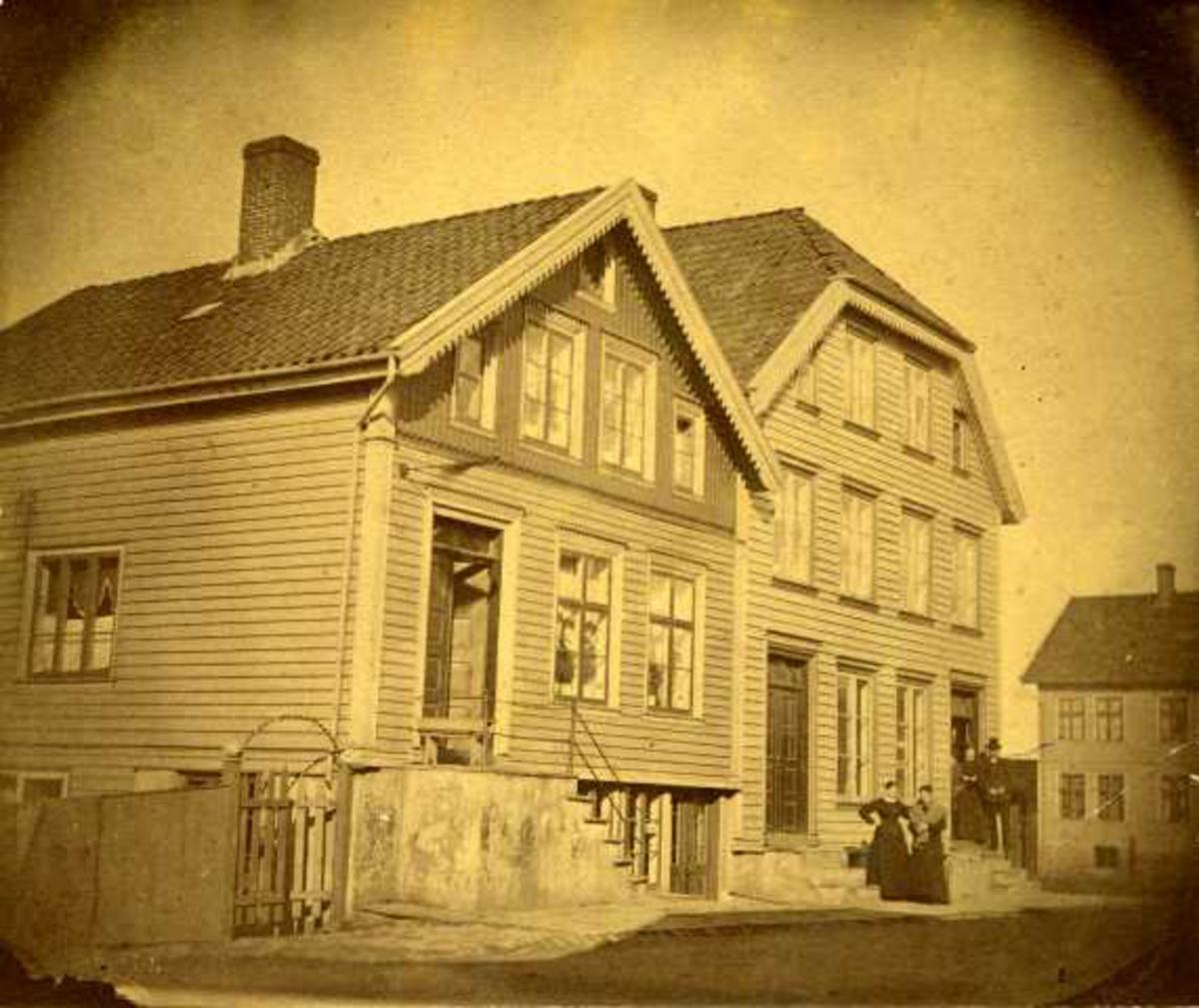Til v. skipper Jens Larsens hus, nåværende Strandgt. 118. Huset er revet eller ombygget. Til h. skipper E. H. Kongshavns hus, Nåværende Strandgt. 120, med brutte gavler. I døren står skipper Ole T. Lindøe, hans søster fru Kongshavn og et gløtt av den yngste i søskenflokken, Svend Lindøe (Ole Johan Lindøe). I bakgrunnen Krohn Haaland Møbelforretning.