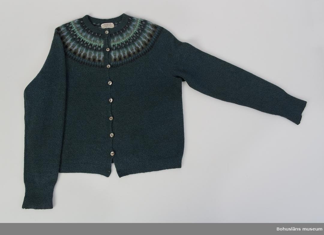 """Kofta med lång ärm i """"nya rundstickningen"""" med mönster Skogsmörkret i sju olika nyanser av grönt, blått samt svart mot en grönblå botten. Åtta ursprungliga knappar (nedersta knappen saknas) samt originaletikett i nacken. Modell av Annika Malmström- Bladini. Välbevarad. Koftan är inköpt åren 1966 eller 1967 på Gillblads i Göteborg eller NK i Stockholm, och är använd tillsammans med mössa UM027885. Givaren har haft många plagg från Bohus Stickning. Hon introducerades via sin man som var sommarboende på västkusten. I gåvoerbjudandet ingick ytterligare sex plagg vilka Insamlingsgruppen tackade nej till då de var krympta och tovade. Ett av dessa plagg, """"Nya Azalean"""" var inköpt i en butik för Bohus Stickning på Fisketången sommaren 1965. Ulla Häglund nämner i boken """"Bohus Stickning 1939 - 1969"""" (1980) att företaget sålde plagg av andrasortering sommartid i Tullboden, senare Gravarne i ombudet Gunhild Wallins bostad. Uppgifterna om Fisketången och Gravare torde avse samma butik.  Plaggen visades i en egenproducerad mindre utställning om Bohus Stickning på Bohusläns museum år 2004.  Se bilagepärm under UM027844 artikel ur tidningen Form, nummer 7 1954, där Annika Malmström och """"Skogsmörkret""""  bl.a. presenteras."""