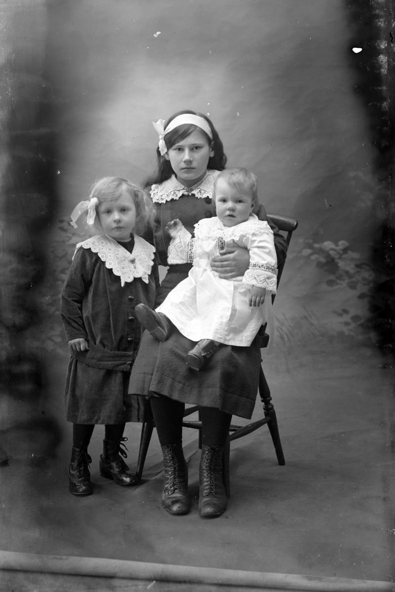 Studioportrett av tre unge jenter i helfigur.