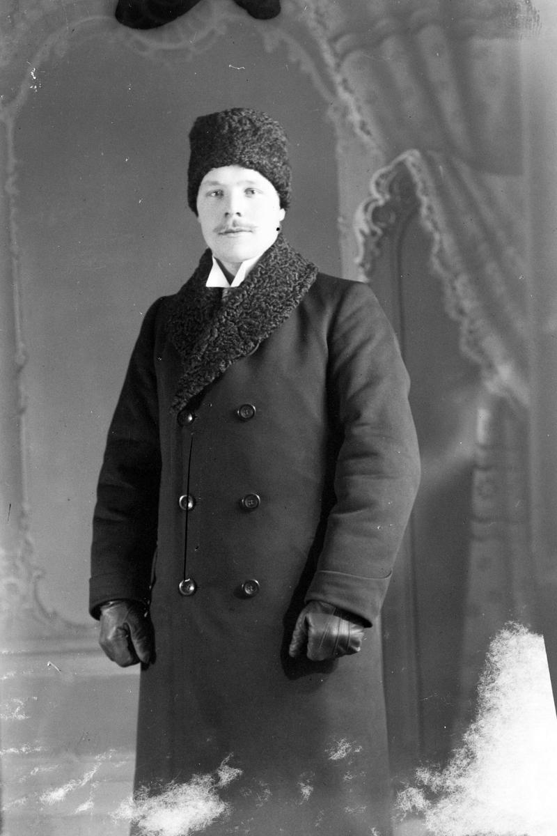 Studioportrett av en mann med pelslue på hodet.