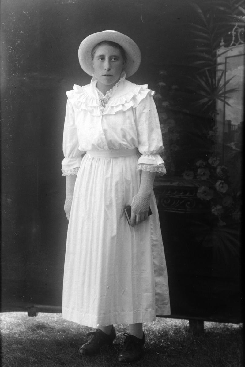Studioportrett av en kvinne i helfigur, trolig Josefine Eriksen.
