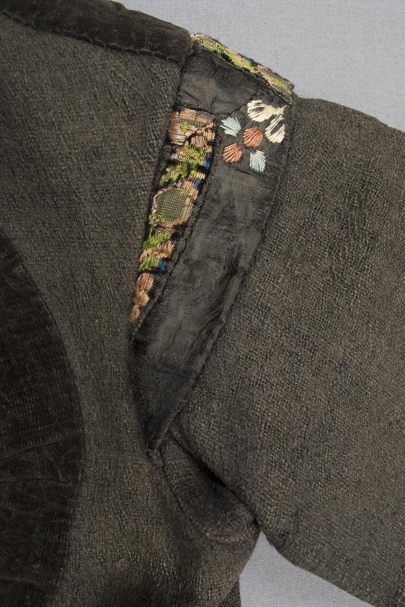 Svart (brunsvart) vadmalströja garnerad med band och broderier. Tröjan har rund öppning fram på bröstet, skört bak och isydda kilar samt axelkarm på ärmen. Runt halsringning och öppningen fram, längs nederkanten på framstycken och ärmar är tröjan dekorerad med tre olika band; ett svart 30 mm brett sidenband, ett svart 30 mm brett sammetsband och ett mönstrat 10 mm brett band med svart sammetsbotten och mönster i rosa och grönt silke. Axelkarmen är dekorerad med ett något bredare snarlika mönstrat band, axelkarmen är också dekorerad med ett svart sidenband och en broderad blomma fram- och baktill. Olika broderade blommor finns också på vardera framstycke, ovanför ärmsprundet samt på bakstycket vid vardera skörtsömmen. Längs två sömmar på bakstycket löper på vardera sidan en flätsöm i svart-på-svart. Framtill knäpps tröjan på två ställen med en hyska och hake. Ryggen är sydd i tre stycken. Ärmlängd: 515 mm. Ärmen är sydd i ett stycke. Ärmsprundet är 105 mm långt och knäpps med en hyska och hake. Axelbredd: 130 mm. Axelkarmen är som bredast 40 mm. Tröjan är helfodrad med handvävt, tuskaftat halvblekt linne. Broderierna är utförda i plattsöm och flätsöm i ljusblått, brunrött och gulaktigt vitt silke. Foder och band är påsydda för hand.