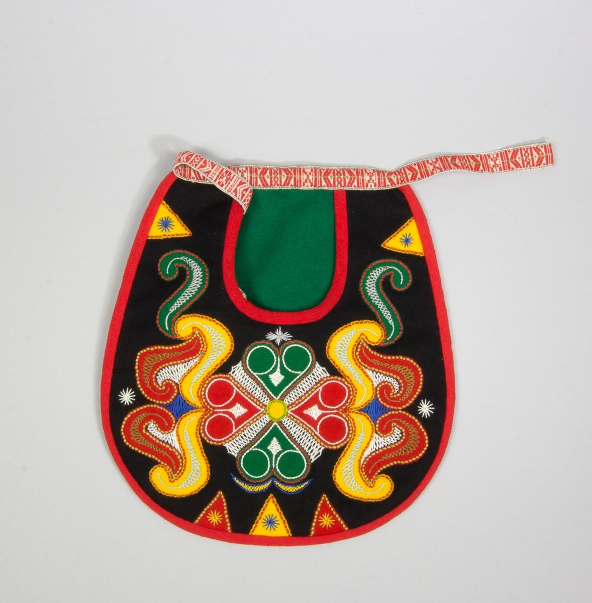 Kjolsäck till dräkt för kvinna från Leksands socken, Dalarna. Modell med u-formad öppning. Framstycke av svart ylletyg, kläde, med applikationer av kläde i rött, grönt och gult, fastsydda med läggsöm. Centralt placerad hjärtblomma med slingor och trekanter på sidorna. Broderi utfört med glansigt bomullsgarn i flera färger: flätsöm, stjälksöm och sticksöm. Kantat runtom med rött diagonalvävt ylleband. Framstycket fodrat med beige bomullstyg. Bakstycke av svart kläde. Midjeband handvävt, med plockat mönster av rött ullgarn på vit botten.