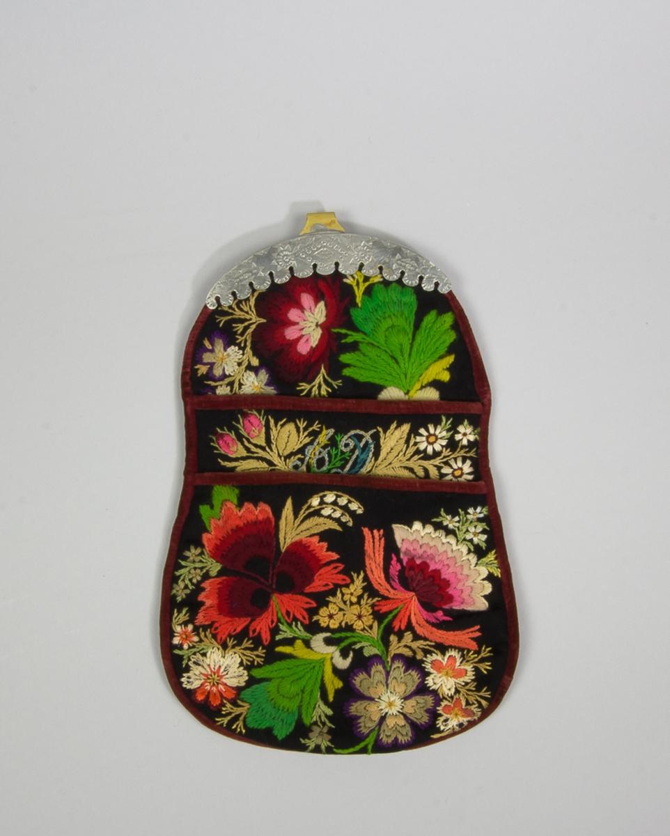 """Kjolsäck till dräkt för kvinna från Floda socken, Dalarna. Modell med två avskurna framstycken. Tillverkad av svart ylletyg, kläde, med broderi, """"påsöm"""", utfört med ull- och silkegarn i många färger, på fram- och överstycken. Motiv: blommor och blad, sydda med plattsöm, stjälksöm, sticksöm och knutar. Märkt A D, inflätat i broderiet på det extra framstycket.  Foder av brunt bomullstyg. Kantat runtom med remsor av brunröd sammet. Bakstycke av samma bruna bomullstyg, tätt maskinstickat i rutor. Beslag av mässing med fast hake och stämplad dekor, förtenning på framsidan.  Haken har en ristad märkning: Skansen 11.321 a(?)."""