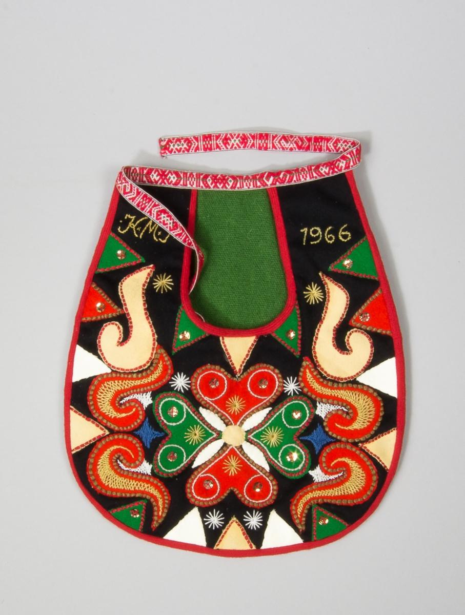 Kjolsäck till dräkt för kvinna från Leksands socken, Dalarna. Modell med u-formad öppning. Framstycke av svart ylletyg, kläde, med applikationer av rött och grönt kläde, gult sämskskinn och vitt fårskinn, fastsydda med läggsöm och kaststygn. Centralt placerad hjärtblomma med slingor och trekanter på sidorna, Broderi utfört med glansigt garn i flera färger: flätsöm, stjälksöm och sticksöm. Sexton paljetter fastsydda, jämnt fördelade. Märkt med stjälksöm på var sida om öppningen: .K.M.S. 1966. Framstycket fodrat med vitt bomullstyg. Kantat runtom med rött diagonalvävt ylleband. Grönt ylletyg i öppningen. Bakstycke av svart kläde. Midjeband troligen handvävt, med plockat mönster av rött garn på vit botten.