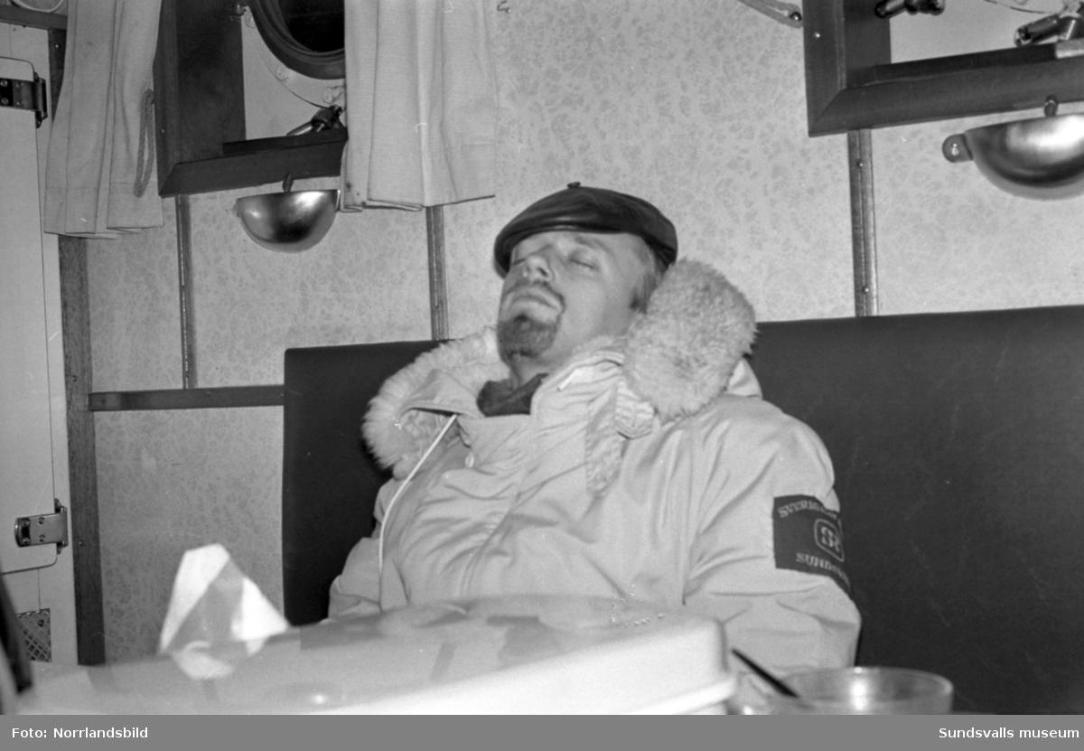 TV-team på plats vid bärgningen av den norska oljetankern Gogstad som den 1 december 1964 strandat vid Bremö kalv utanför Sundsvall. Den 9 december bröts fartyget itu i en sydlig storm. Den 12 december drogs akterskeppet loss och den 16 december drogs förskeppet loss.