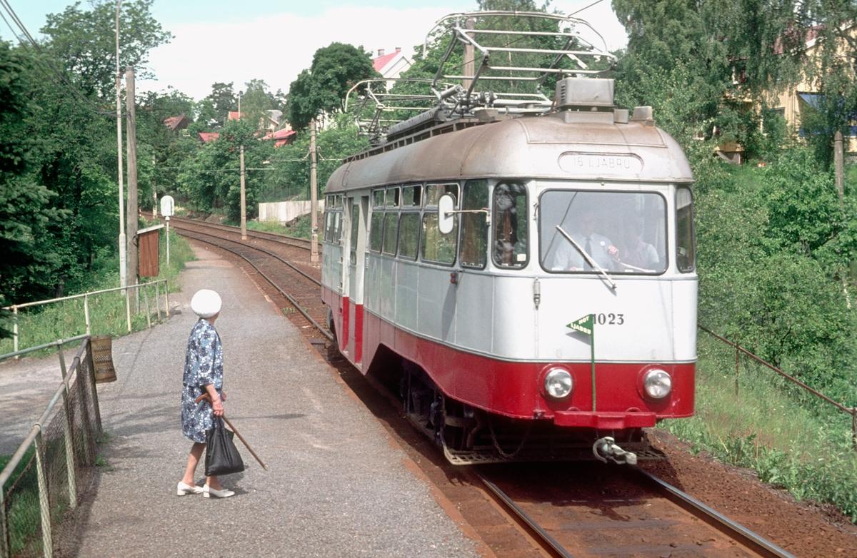 Ekebergbanen, Oslo Sporveier. Vogn 1023 på Sæter. Signalanlegg ute av drift, kjøring med togstav. Eldre dame venter på trikken.