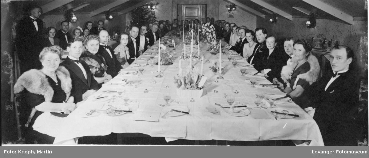 Festkledde mennesker ved bordet