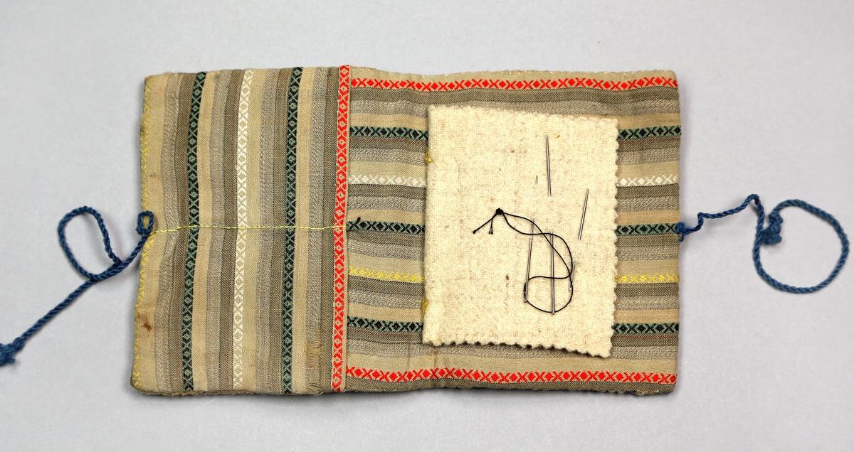 Liten mappe med lomme på innsida og et lite tøystykke av ull som er sydd fast i midten, og som det er tredd nåler på. Utsida av mappa er brodert med korssting. Mappa er fôret med et vevd flerfarga tøy
