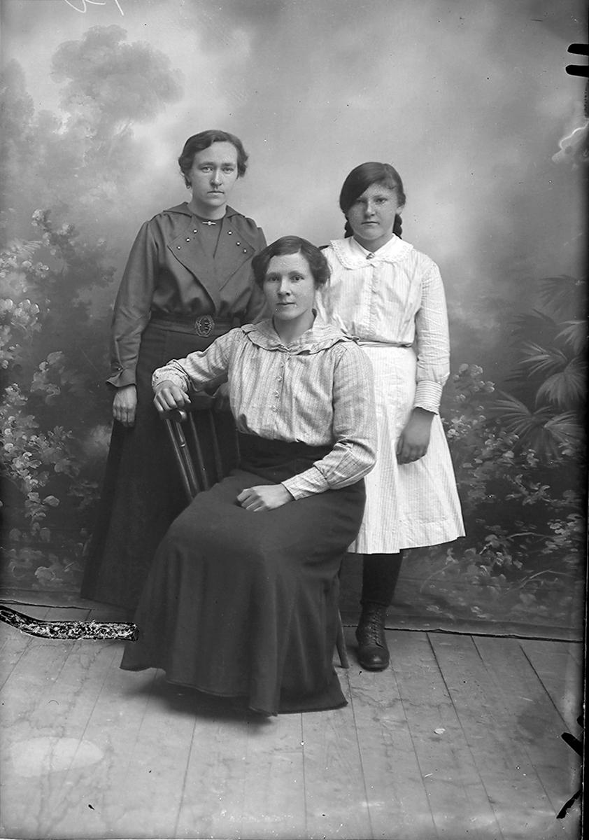 Portrett. Tre kvinner. En sitter på en stol, to står bak.Bildet er tatt på Inndyr.