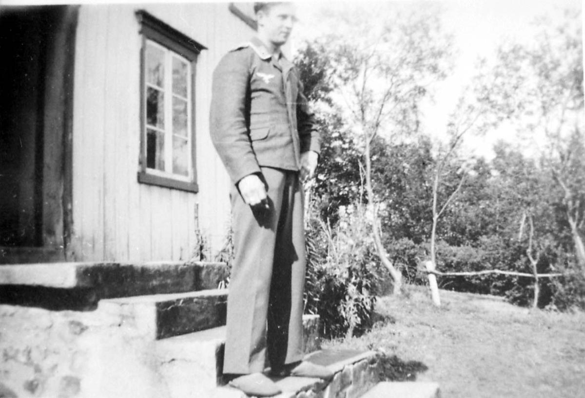 Portrett. 1 person, mann i militæruniform. Utendørs ved ei bygning.