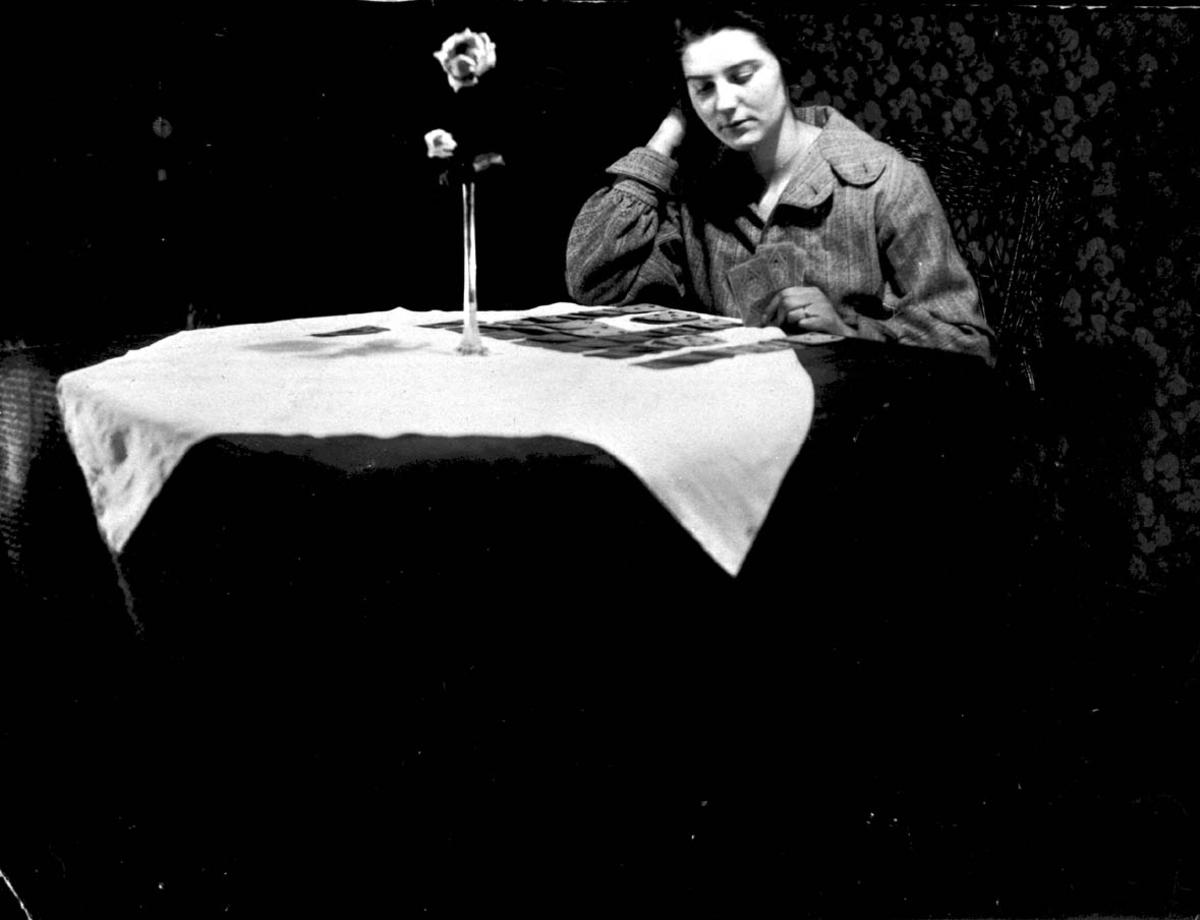 Portrett. 1 person, kvinne sitter ved et bord. Innendørs