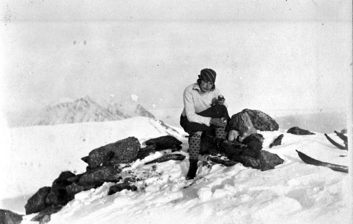 Portrett, 1 person, kvinne, sitter på fjelltopp. Spiser. Ski ved siden av. Snø.