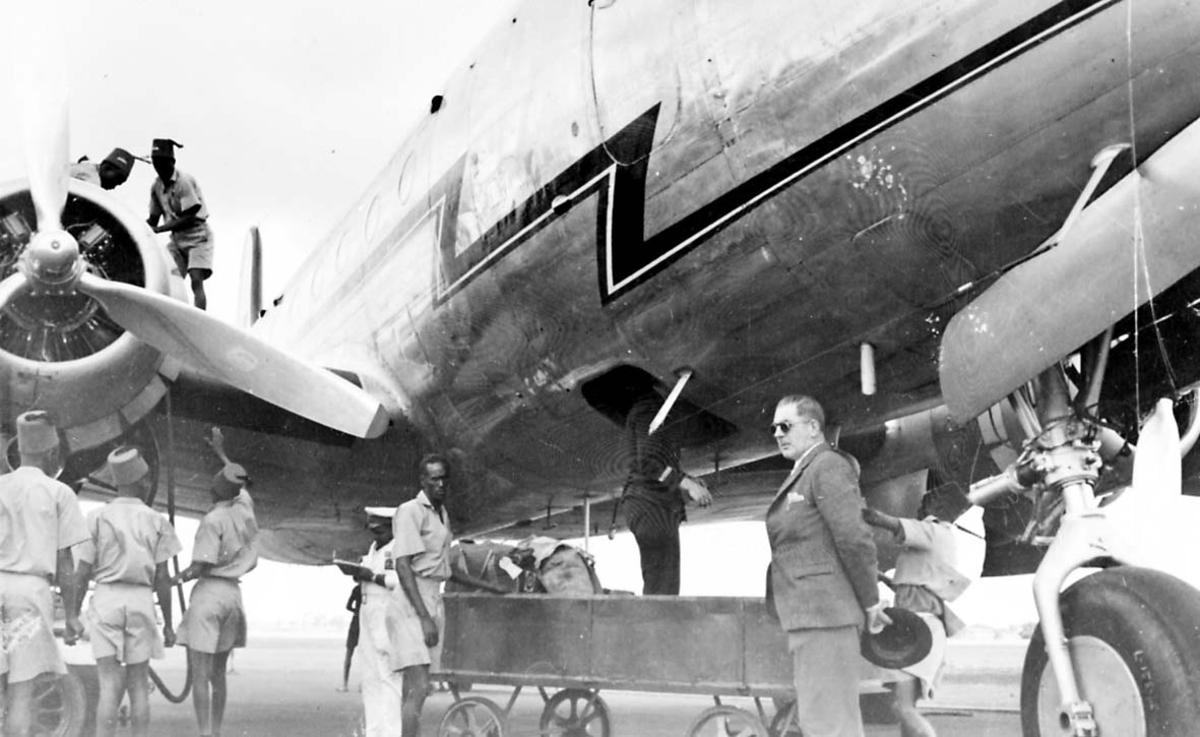 Lufthavn. 1 fly på bakken Douglas DC-4 C-54A fra Braathens SAFE. Noen personer ved flyet.