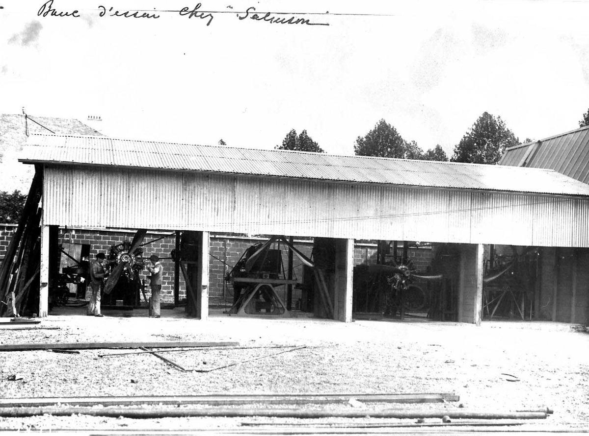 """Bygning med fire """"åpne"""" rom. Flere Salmson flymotorer i bygningen. To personer, menn, i ferd med å montere en av motorene på et fly."""