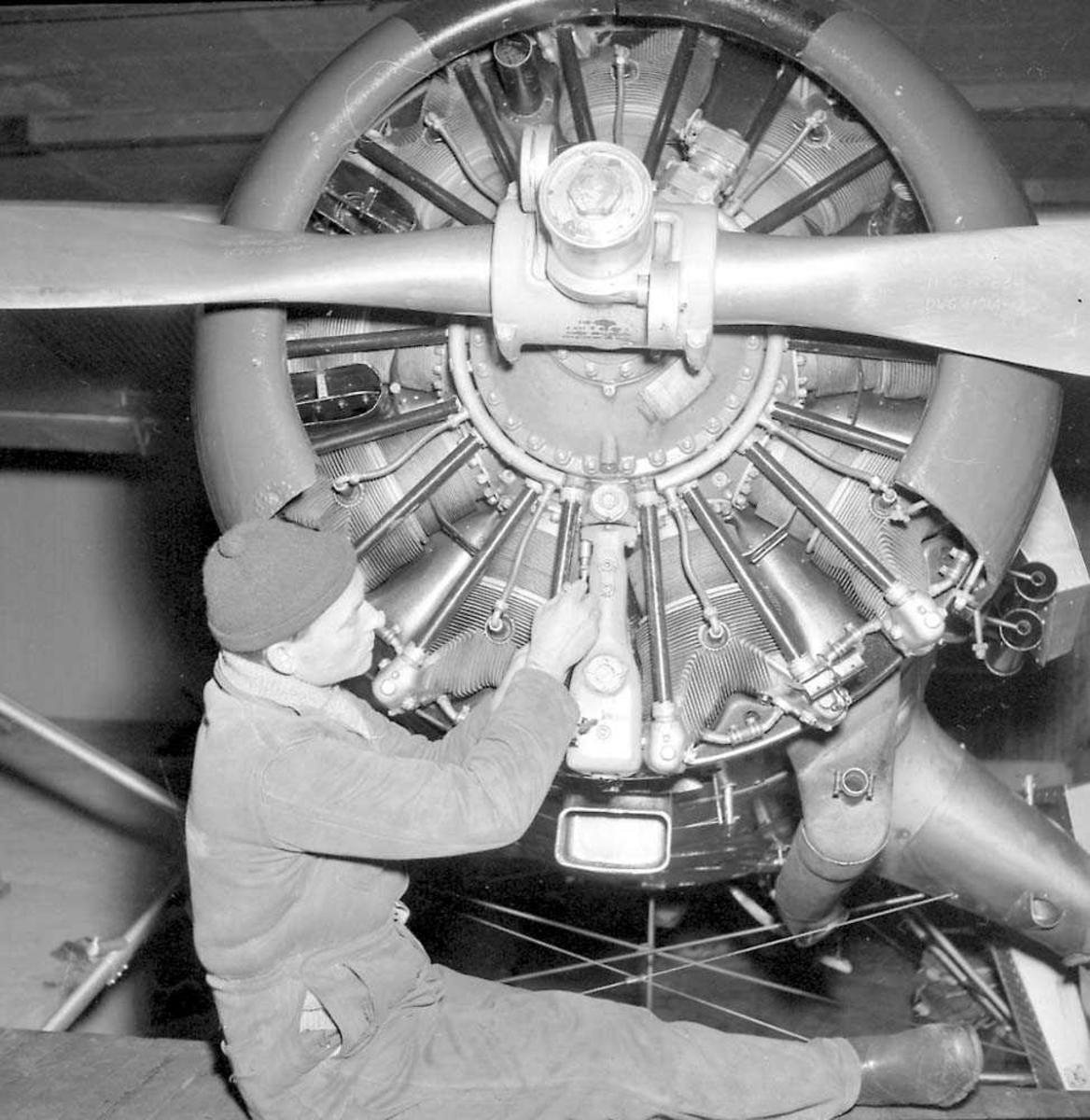En person som driver med vedlikehold på en flymotor til Norseman.