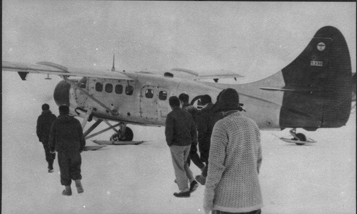 Ett fly på isen, Otter OAF. Mange personer ved flyet.