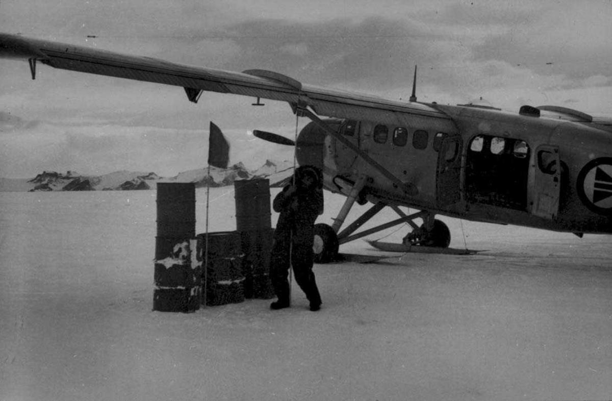 """Ett fly på isen, Otter. En person """"planter"""" det Norske Flagg i isen. Noen bensinfat ved flyet."""