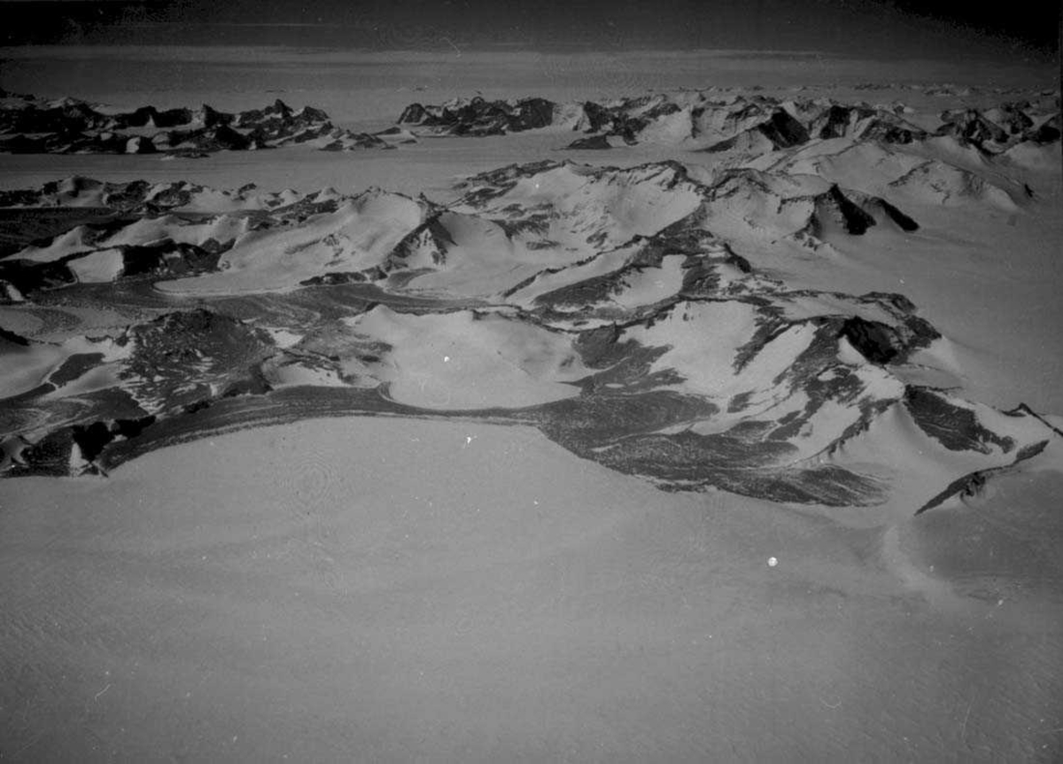 Luftfoto. Snødekt landskap med fjelltopper.
