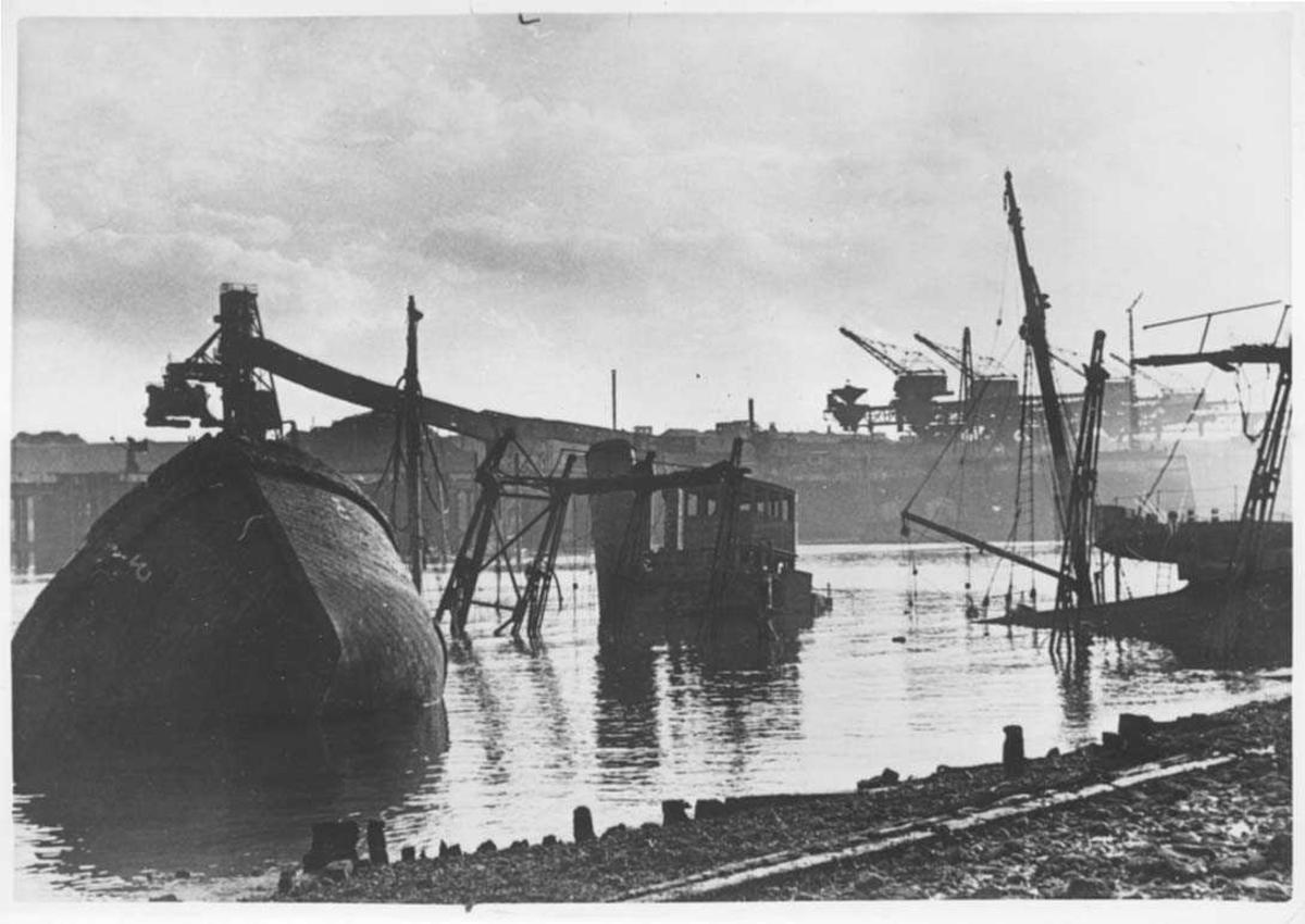 Flere skip som ligger nedsunke i vannet etter bombing.