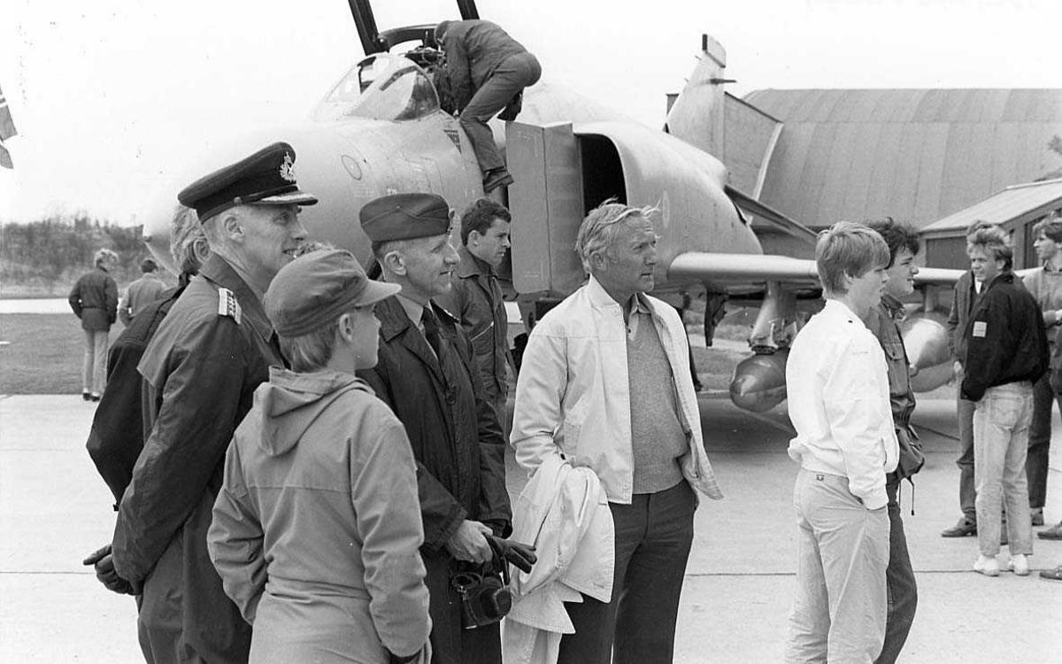 Sivile og militære personer foran et militært jagerfly.