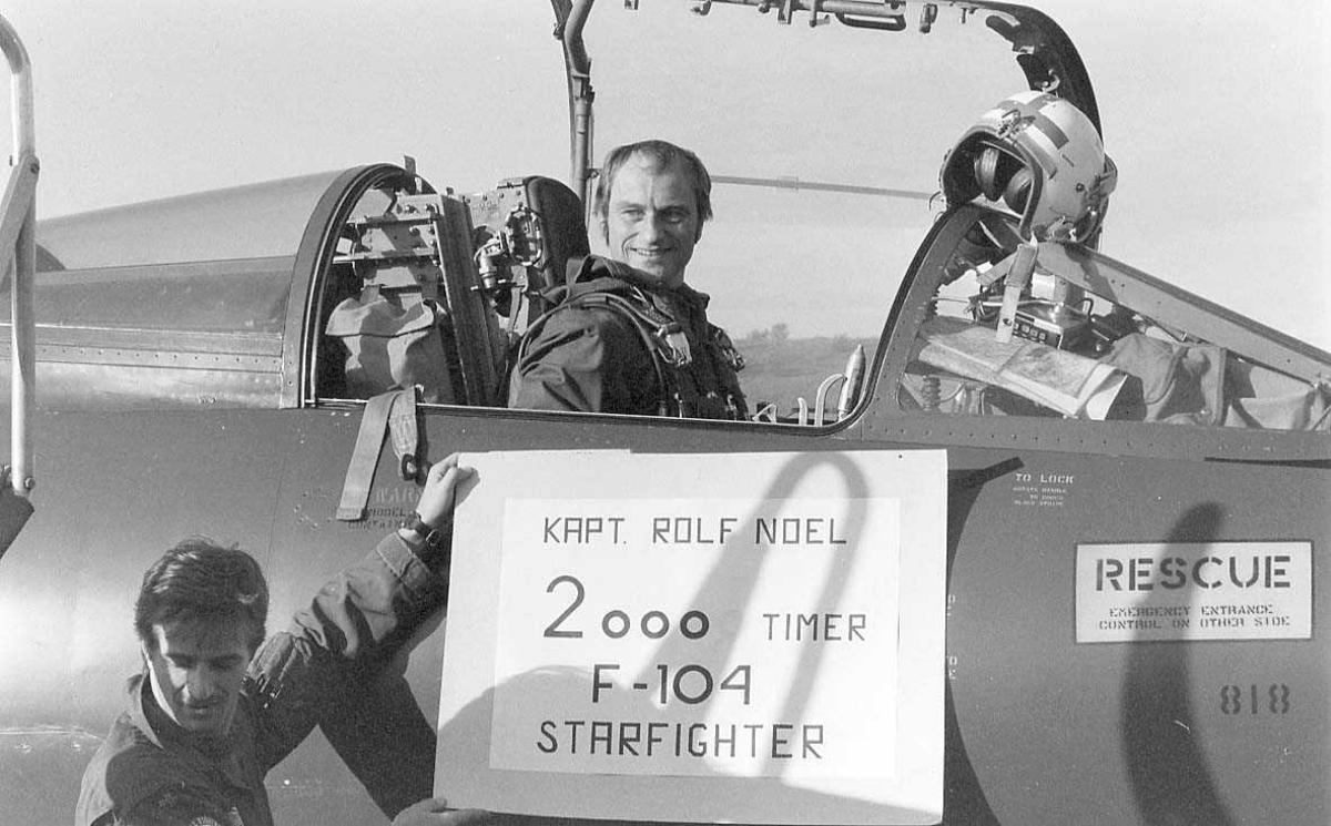 En person i cockpit'en og en person på utsiden av et fly.