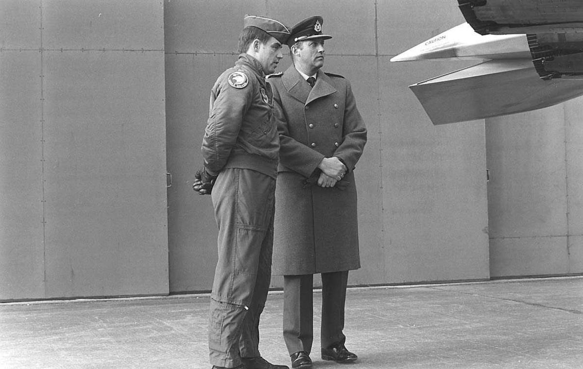 2 personer bak et fly. En hangar i bakgrunnen.