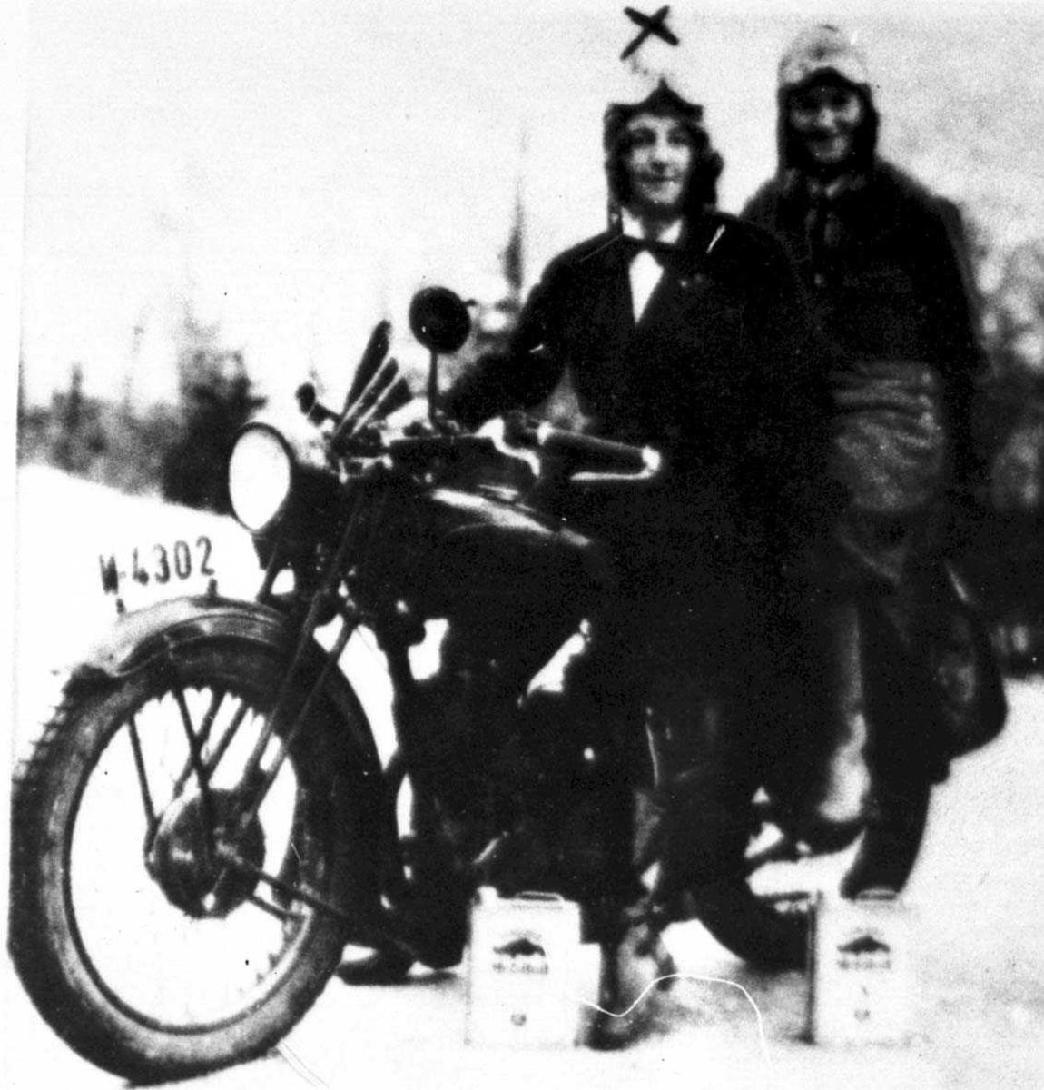 To kvinner på en motorsykkel. Motorsykkelen er en AJS 350 - kubikkcentimeter.